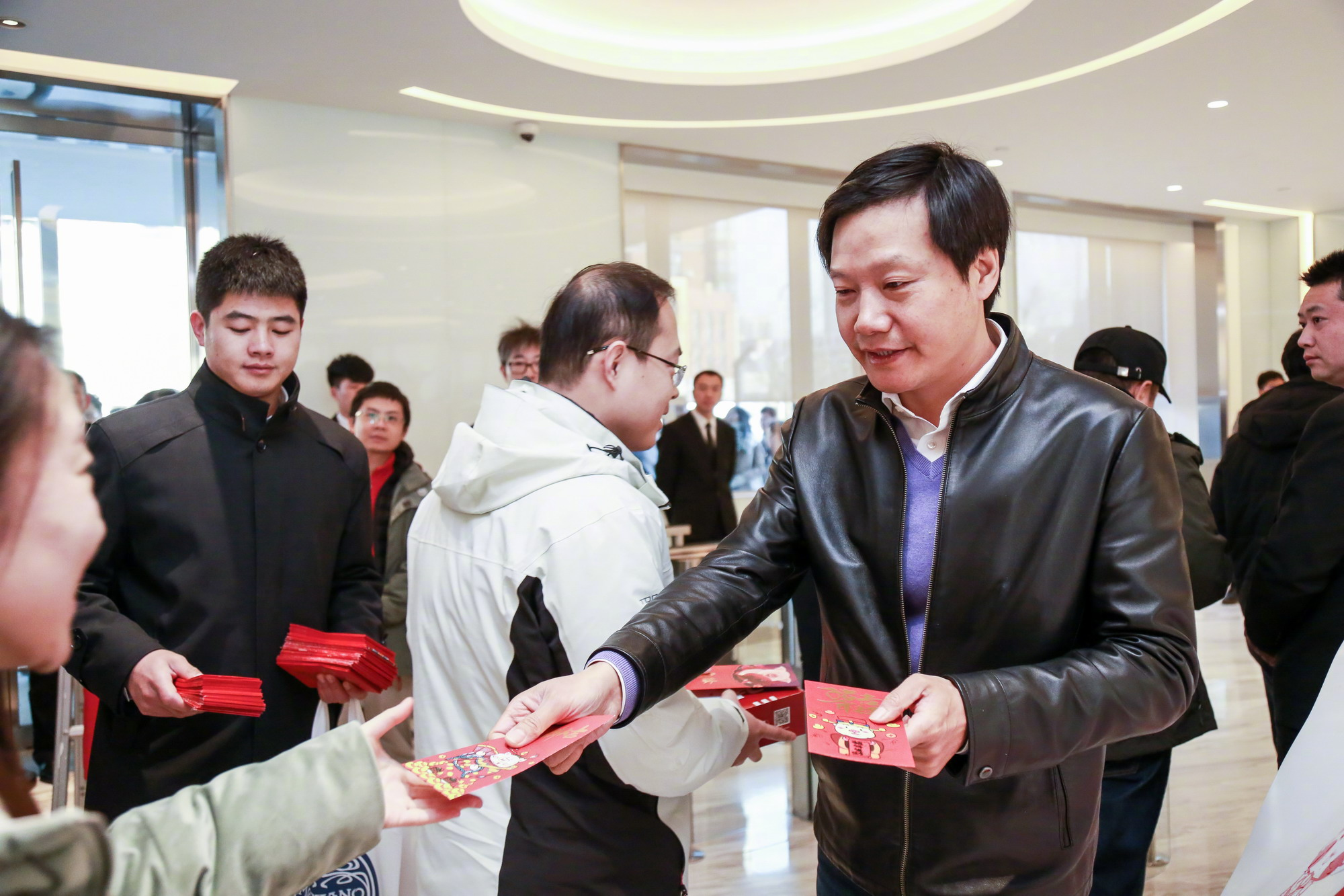 Lei Jun entregando sobre rojo a sus empleados